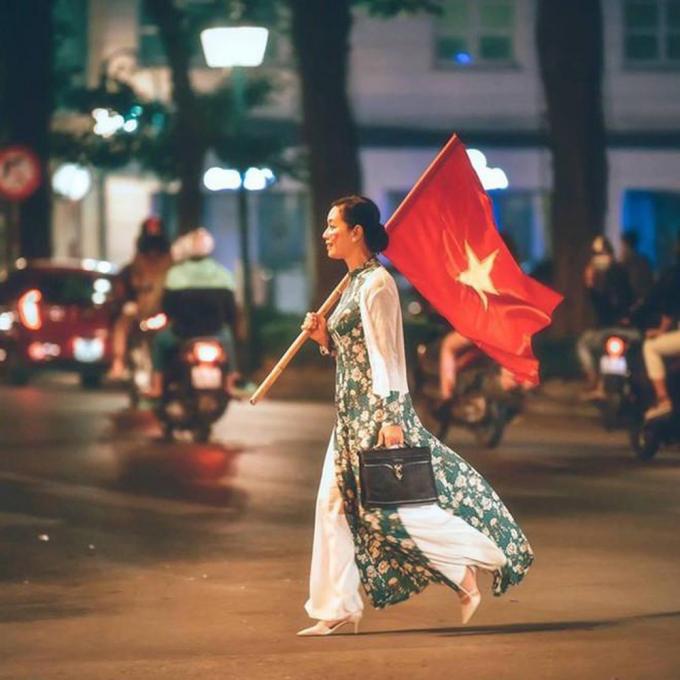 NSƯT Chiều Xuântrong tàáo dài, cầm cờ Việt Nam đi