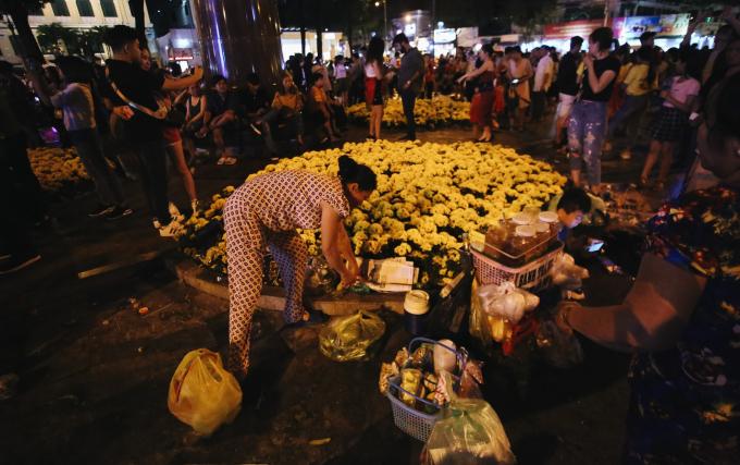 Một số người bán hàng rong tự ý để đồ dùng quanh bồn hoa, khiến không ít hoa bị gãy, dập. Nguồn: kenh14.vn
