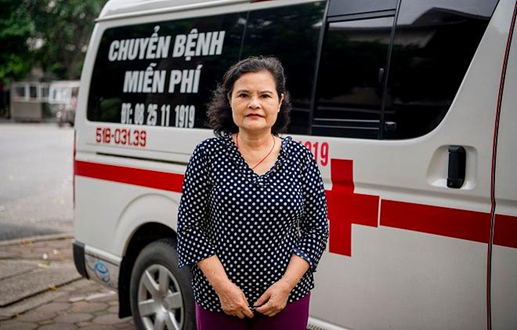 Bà Phan Thị Bính bên cạnh chiếc xe cứu thương chuyển bệnh nhân miễn phí, hỗ trợ hàng trăm người bệnh có hoàn cảnh khó khăn.