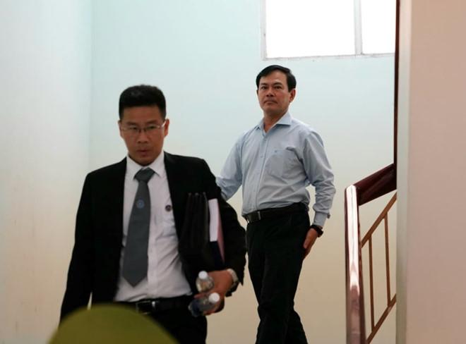 Bị cáo Nguyễn Hữu Linh (đi sau) và luật sư bào chữa, rời tòa sau khi hoãn xét xử.