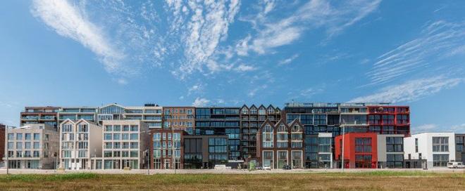 Nằm tại thủ đô Amsterdam của Hà Lan, quần thể kiến trúc này hoạt động giống như một thành phố mini, bao gồm 2000 đơn vị nhà ở, 70 nhà thuyền, một trường học, một khách sạn và một trung tâm y tế.