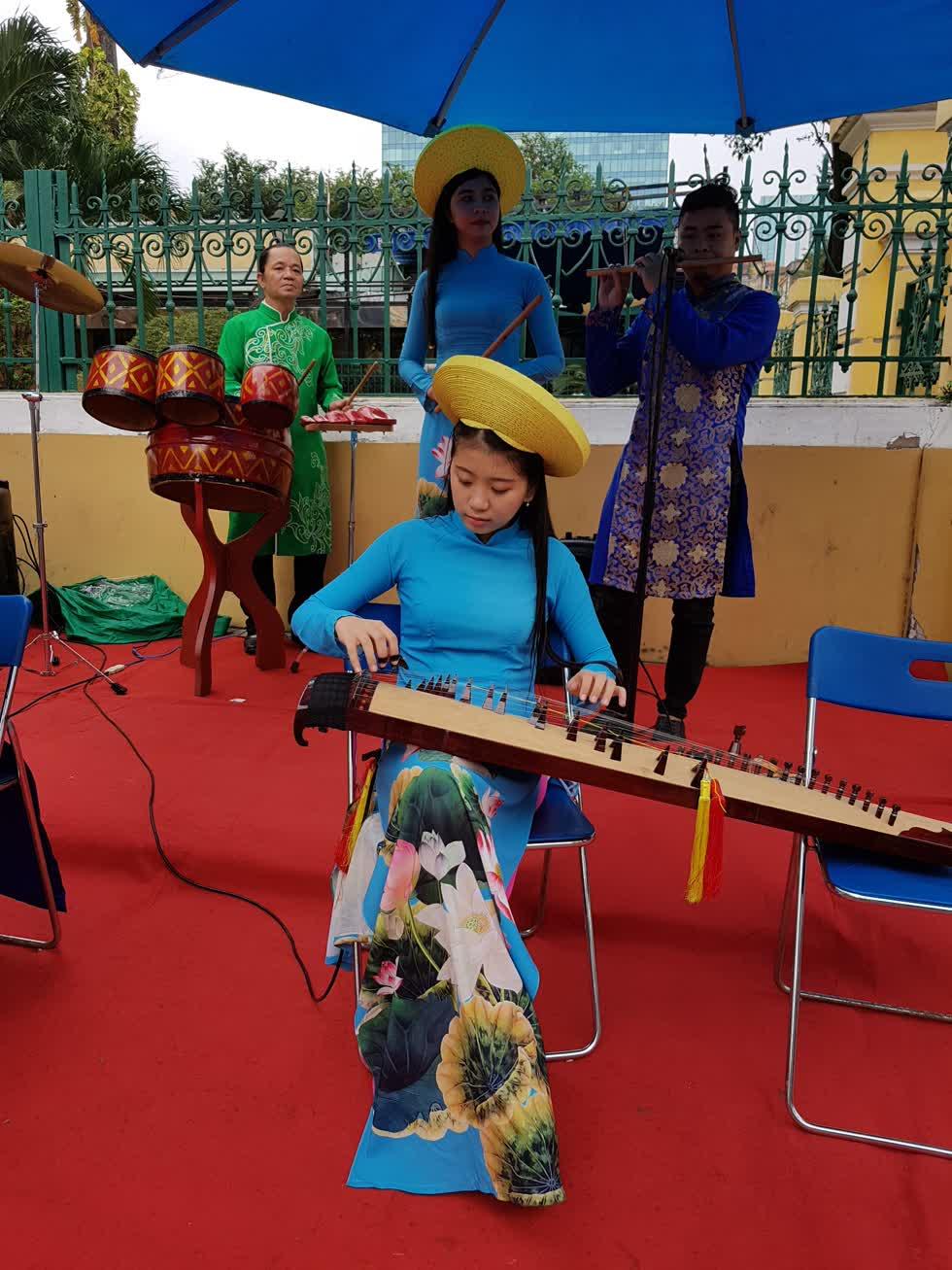 Thùy Trang chơi đàn trước bưu điện Thành phố - Ảnh: Cẩm Viên