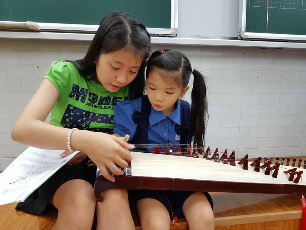 Thùy Trang dạy đàn cho các em nhỏ ở trường Hòa Bình - Ảnh: Cẩm Vien