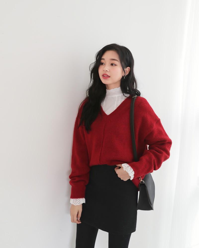 Sẵn áo len đỏ cổ V đơn giản, bạn có thể diện thêm một chiếc sơ mi cổ cao thật điệu bên trong, phối cùng chân váy mini là đã có ngay một set đồ đi chơi Noel đúng chất tiểu thư.