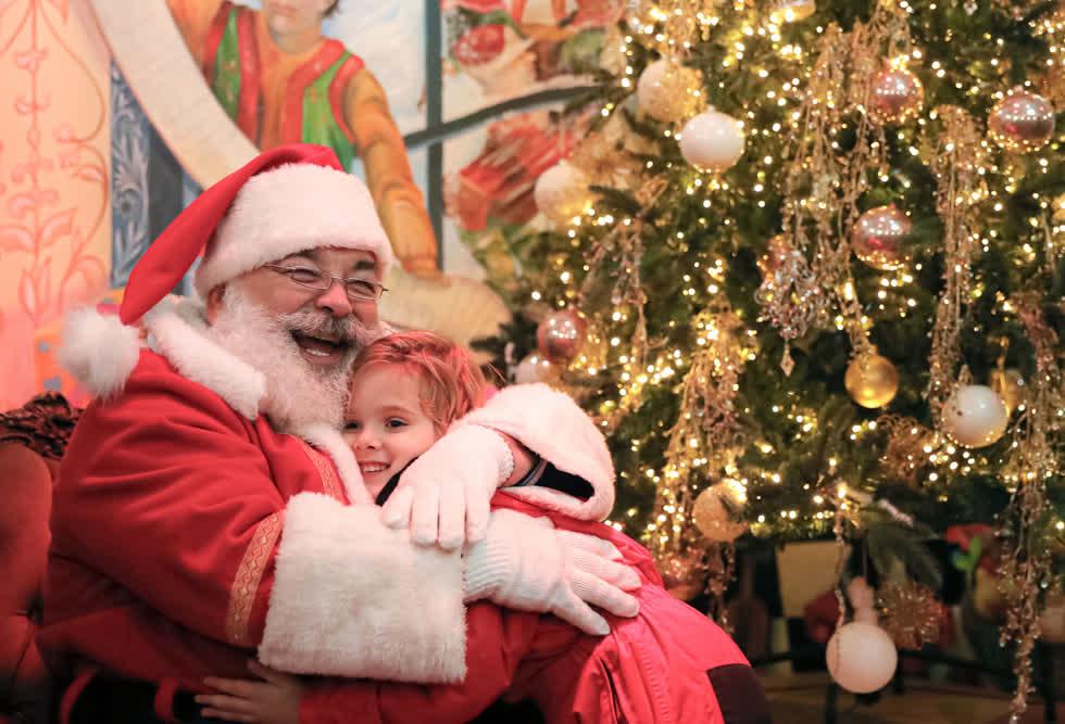 Một ông già Noel ôm một đứa trẻ tại một hội chợ Giáng sinh ở Bucharest, Romania, vào ngày 13/12 vừa qua. Hàng trăm trẻ em đã chờ đợi để cùng cha mẹ đến gặp ông già Noel và nhận một cây kẹo mút tại hội chợ ở thủ đô Rumani. Ảnh AP.