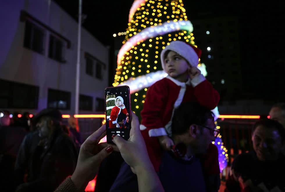 Một đứa trẻ trong trang phục ông già Noel được chụp ảnh khi mọi người tụ tập quanh một cây thông Giáng sinh được chiếu sáng ở thành phố Gaza, Gaza vào ngày 3/12. Ảnh:Getty.