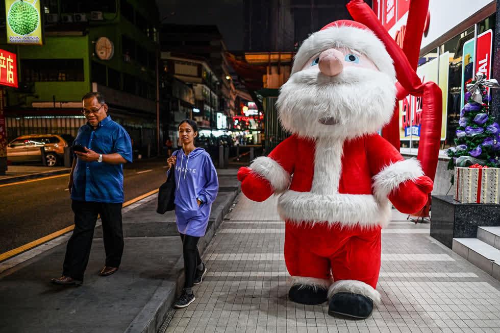 Người đi bộ đi ngang qua một người đàn ông mặc trang phục ông già Noel khổng lồ bên ngoài một trung tâm mua sắm ở Kuala Lumpur vào ngày 11/12. Ảnh:AFP / Getty.