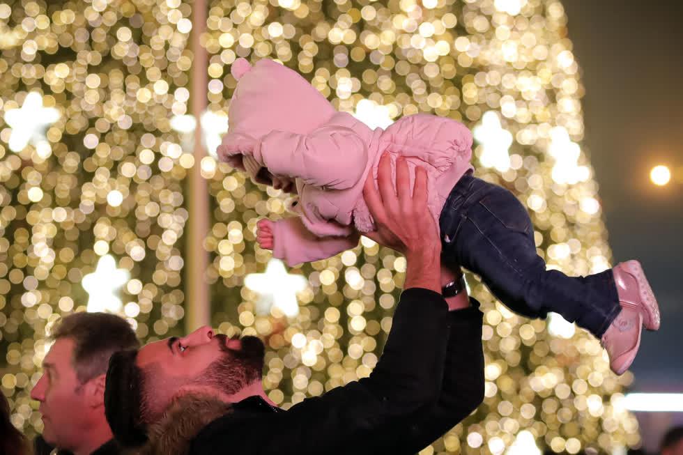 Một người đàn ông nâng một đứa trẻ gần đèn trang trí tại một hội chợ Giáng sinh ở Bucharest, Romania, vào ngày 13/12. Ảnh: AP.