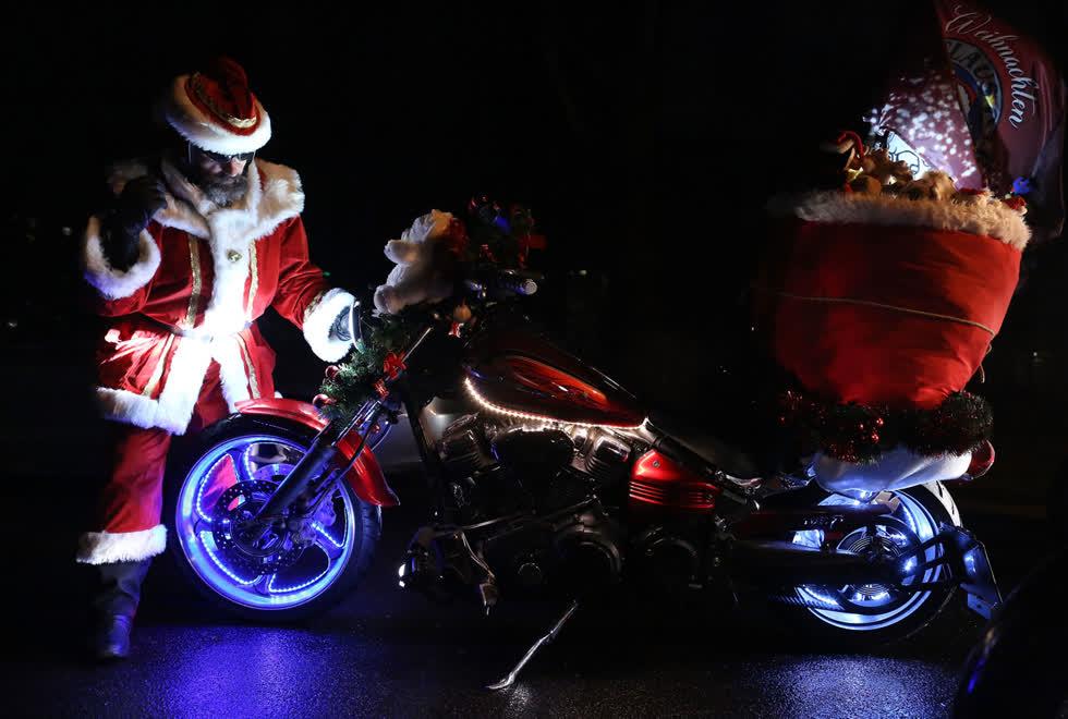 Một người lái xe mô tô hóa trang thành ông già Noel sửa chữa đèn pha trong Lễ hội Giáng sinh Berlin lần thứ 22 vào ngày 14/12 vừa qua tại Berlin, Đức.Khoảng 100 người đi xe máy hóa trang thành ông già Noel, tuần lộc và các thiên thần cưỡi mô tô trang trí đèn Giáng sinh trên khắp thành phố trong một buổi gây quỹ hàng năm cho người nghèo. Ảnh:Getty.
