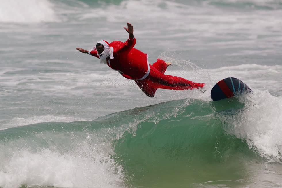 Carlos Bahia, hóa trang thành ông già Noel, lướt sóng tại bãi biển Maresias ở Sao Sebastiao, Brazil, vào ngày 15/12. Ảnh:Reuters.