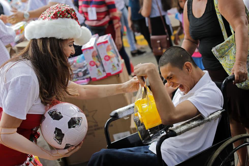 Chủ tịch của Tổ chức Chăm sóc trẻ em bị bỏng (APROQUEN), Vivian Pellas (trái), tặng một món quà Giáng sinh cho một thanh niên tại Bệnh viện Vivian Pellas ở Managua, Nicaragua, vào ngày 12/12. Ảnh:AFP / Getty.