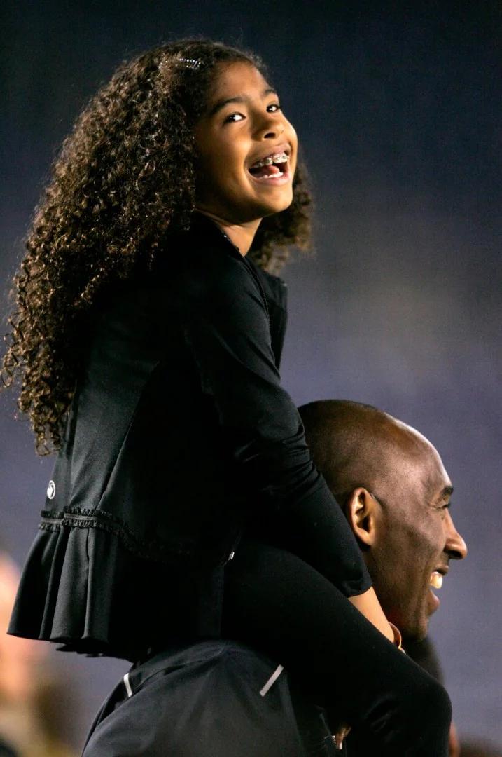 Bức ảnh này được chụp vào năm 2014 tại CLBLos Angeles Lakers,Kobe Bryant đứng bên lề với cô con gái Gianna Maria-Onore Bryant trên vai trước khi bắt đầu trận đấu với Mỹ và Trung Quốc tại SVĐ Qualcomm ở TP. San Diego, bang California. Ảnh: AFP.