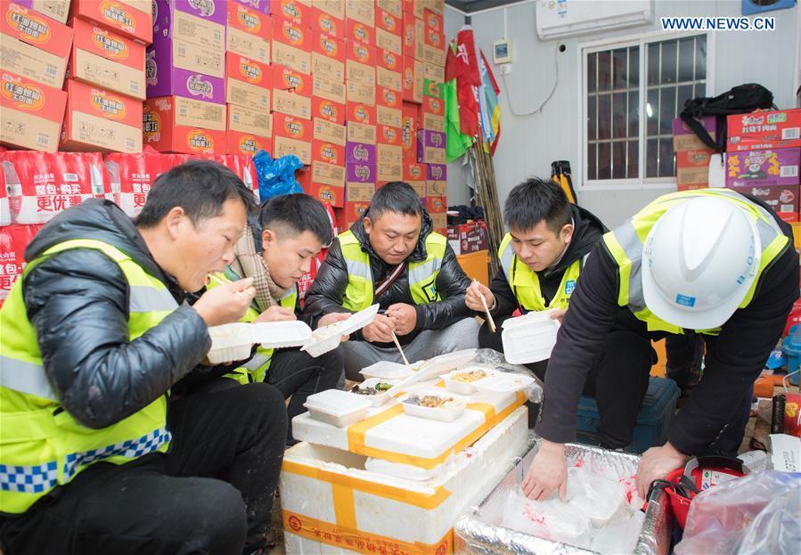 Công nhân dùng bữa tại nhà kho của một bệnh viện tạm thời ở Vũ Hán, trung tâm tỉnh Hồ Bắc của Trung Quốc, ngày 24/1/2020. Bệnh viện tạm thời dự kiến sẽ cung cấp nguồn lực y tế để điều trị cách ly và cho bệnh nhân viêm phổi.(Tân Hoa Xã / Xiao Yijiu)