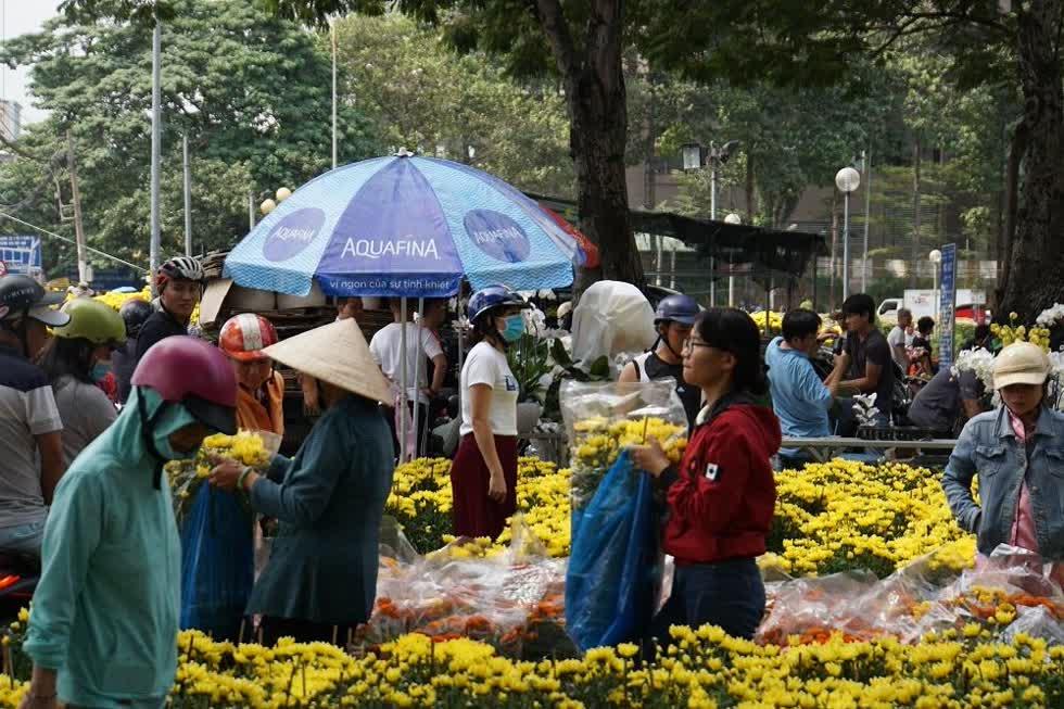 Cảnh mua bán khẩn trương hơn giữa trưa khi ban quản lý chợ hoa liên tục phát loa thông báo các tiểu thương chuẩn bị hoàn trả mặt bằng.