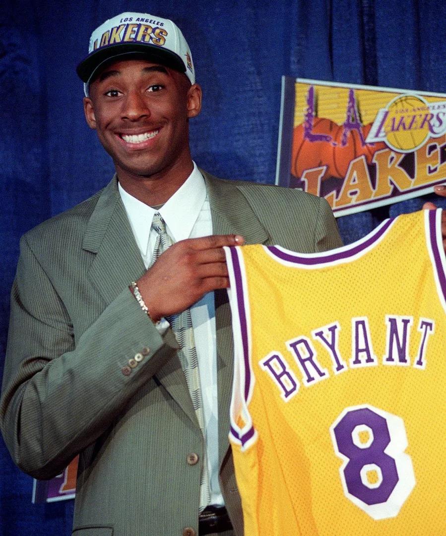 Bức ảnh chụp ngày 12/7/1996 khi anh 17 tuổi.Kobe Bryan đã nói đùa với giới truyền thông khi anh cầm chiếc áo của độiLos Angeles Lakers trong cuộc họp báo diễn ra tại Great Western ở Inglewood, California. Ảnh: AP.