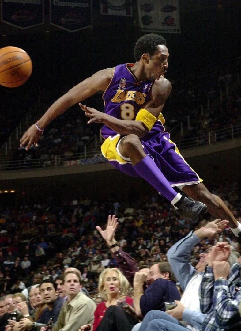 Ảnh chụp năm 2001,Kobe Bryan đã nhảy qua một hàng rào người ham mộ sau khi cứu bóng ra khỏi giới hạn trong trận cầu Laker 107-101 trước Houston Rockets ở Houston. Ảnh: AP.