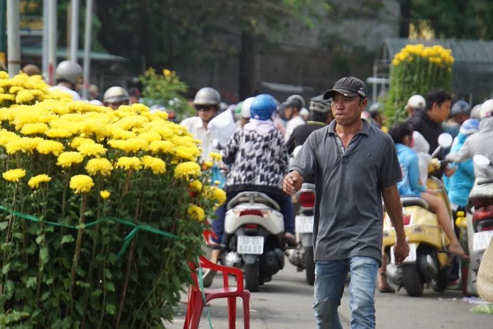 Anh Sơn (41 tuổi, quê Khánh Hòa) buồn bã cho biết đưa vào Sài Gòn gần 300 chậu hoa cúc các loại nhưng bán chưa được một nửa.