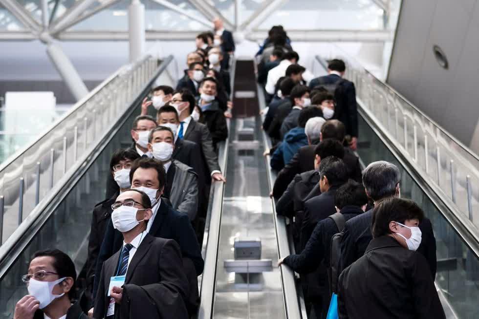 Người Nhật Bản đeo khẩu trang bên ngoài một nhà ga ở Yokohama.