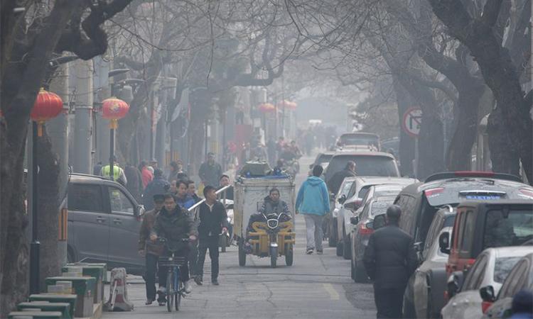 Người dân đi lại trong làn khói mù ô nhiễm tạimộtphố cổ ở Bắc Kinh.