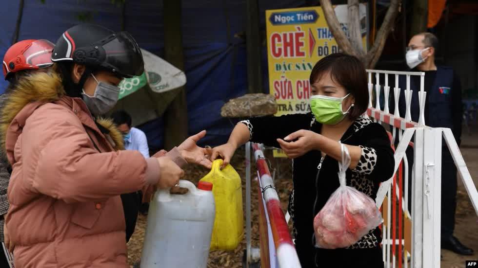 Người dân truyền nhau những can nước và thực phẩm tại một chốt kiểm soát ở Sơn Lôi.