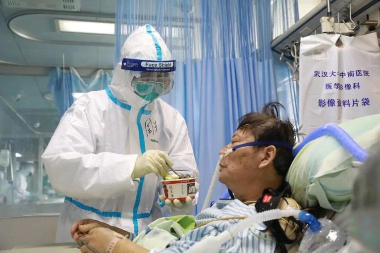 Y tá mặc đồ bảo hộ đang chăm sóc một bệnh nhân nhiễm virus corona tại khu cách ly của bệnh viện ở Vũ Hán. Ảnh:Reuters.