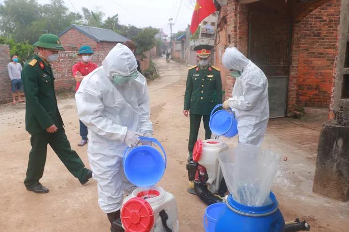 Lực lượng chức năng phun dung dịch khử trùng tại địa phương. Ảnh: NLD.