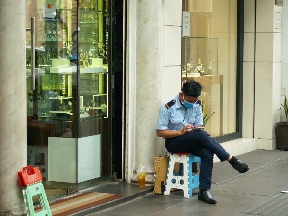 Nhân viên bảo vệ một cửa hàng có thời gian để lướt điện thoại, cảnh tượng hiếm thấy so với ngày thường.(Ảnh: Tri Thức)