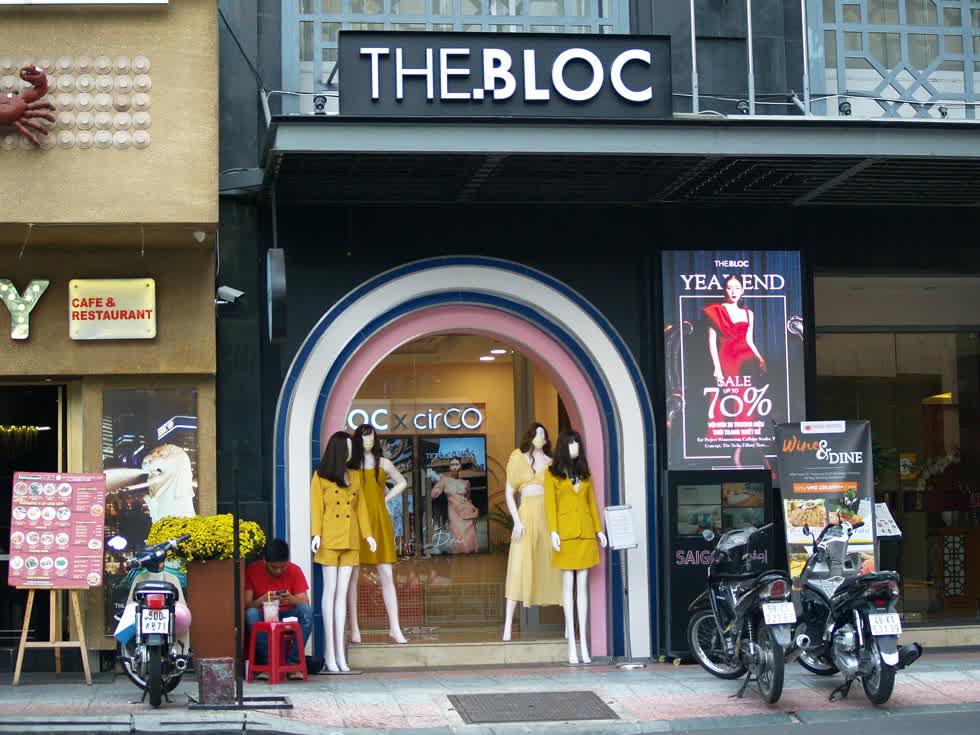 Các cửa hàng trên đường Đồng Khởi mua bán đìu hiu, nhân viên ngoài cửa hàng ngồi bấm điện thoại giết thời gian.(Ảnh: Tri Thức)