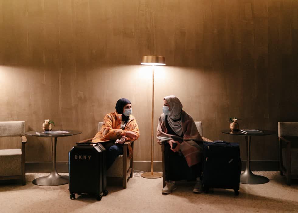Emy, trái và Macha, phải, từ Kuwait, đeo khẩu trang trong khi chờ đợi để nhận phòng tại một khách sạn ở Milan vào thứ Hai.Họ nói rằng vali của họ chứa đầy khẩu trang.
