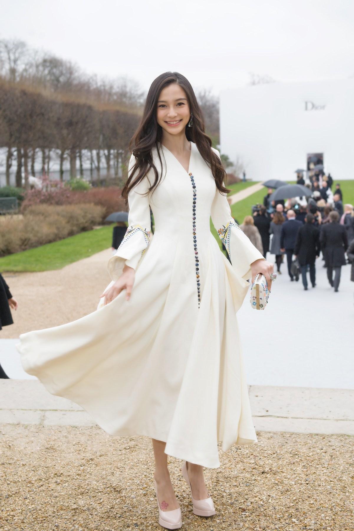 Bộ váy trắng cổ V với hàng cút màu sắc làm điểm nhấn là lựa chọn của Angelababy khi tham dự buổi trình diễn Dior Thu – Đông 2015. (Ảnh: Sina)