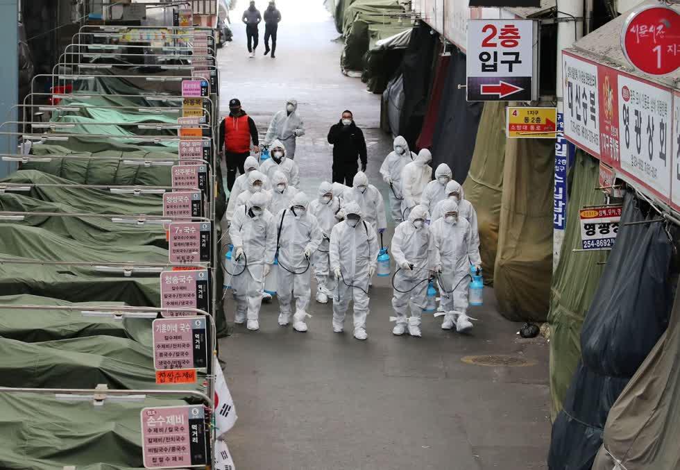 Nhân viên y tế phun thuốc khử trùng vào hôm nay tại một khu chợ ở Daegu, thành phố phía đông nam nơi có nhiều ca nhiễm COVID-19. ảNH: Yonhap,
