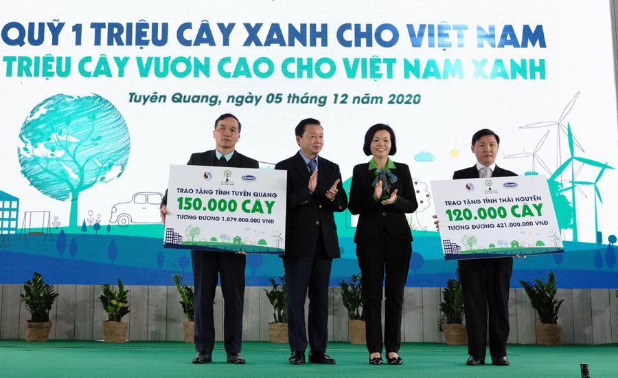 Bộ trưởng Trần Hồng Hà và bà Bùi Thị Hương - Giám đốc Điều hành Hành chính - Nhân sự - Đối ngoại, Công ty Cổ phần Sữa Việt Nam trao biểu trưng tặng cây cho 2 tỉnh Tuyên Quang và Thái Nguyên.
