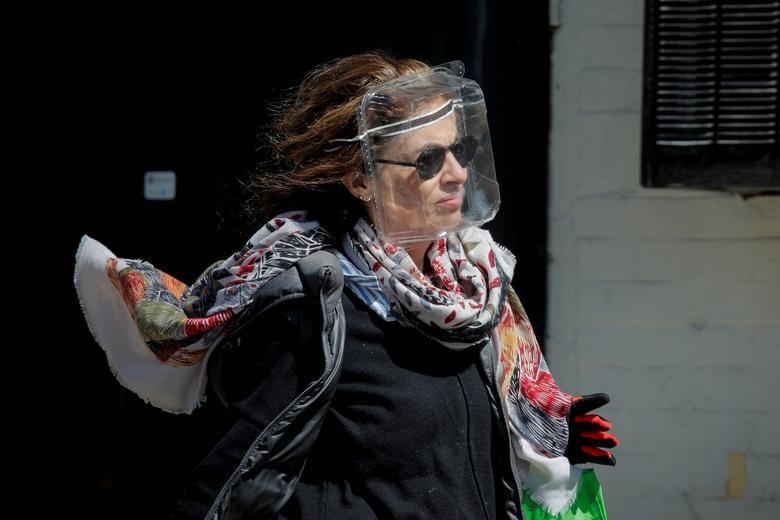 Một người phụ nữ đeo mặt nạ chống giọt bắn bằng nhựa để bảo vệ trong khi dịch COVID-19 bùng phát ở Brooklyn, thành phố New York (ảnh trái) và Mọi người đi bộ ở Quảng trường Thời đại, Manhattan, phía trên là một số màn hình được chiếu sáng màu xanh lam như một phần của sáng kiến 