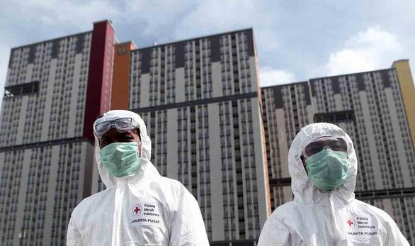 Nhân viên Hội Chữ thập đỏ Indonesia bên ngoài làng vận động viên Kemayoran được hoán cải thành bệnh viện dã chiến điều trị bệnh nhân COVID-19 - Ảnh: AFP.