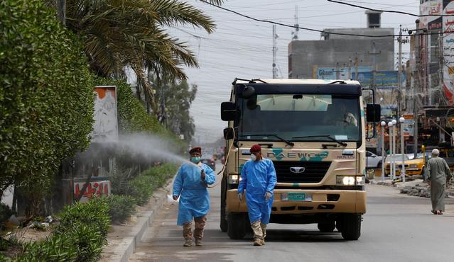 Quân đội Iraq mặc một bộ đồ bảo vệ phun thuốc khử trùng để vệ sinh đường phố, trong giờ giới nghiêm. Ảnh:REUTERS.