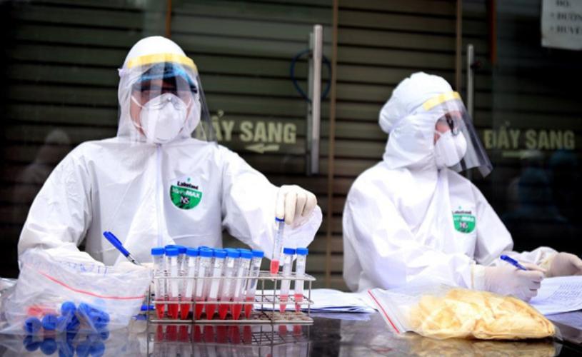 Nhân viên y tế lấy mẫu xét nghiệm sàng lọc COVID-19 ở thôn Hạ Lôi. Ảnh: TTXVN.