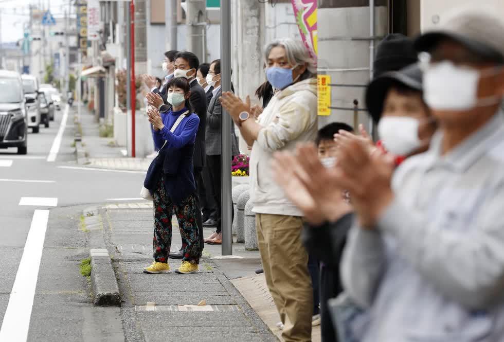 Một nhóm người ở tỉnh Shizuoka đứng trên vỉa hè để vỗ tay thể hiện sự ủng hộ với các nhân viên y tế - hành động rất phổ biến ở châu Âu trong thời kỳ đại dịch. Ảnh:AP.