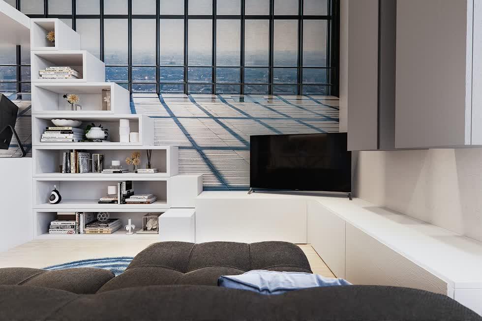 Ti vi ở góc, các bước trên giường gác xép biến thành một kệ mở và tủ tùy chỉnh với lưu trữ rộng rãi trong khu vực sinh hoạt.