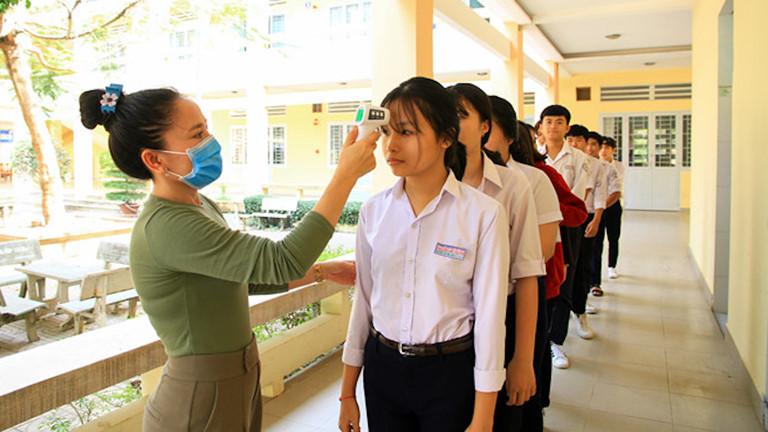 Tiến hành đo thân nhiệt cho học sinh trước khi vào lớp học để đảm bảo an toàn sức khỏe.