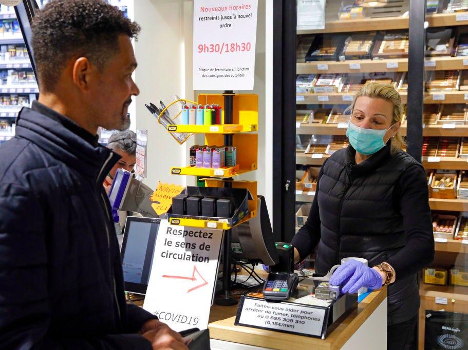 Một nhân viên cửa hàng thuốc lá đeo khẩu trang và găng tay bảo hộ tại Pháp.