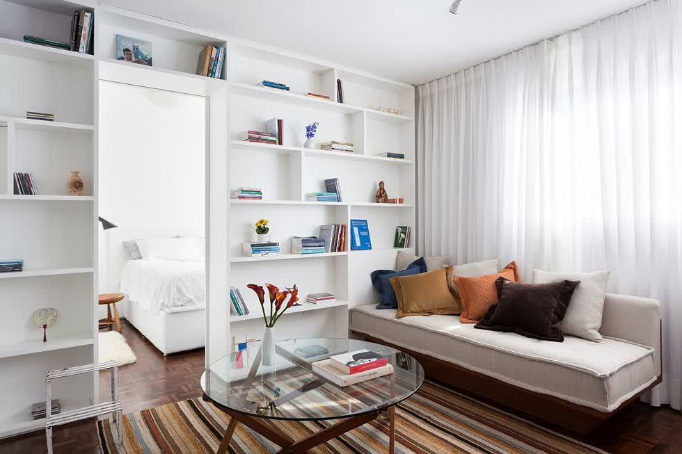 Trước tiên là thiết kế phòng khách củacăn hộ 30m2được bài trí tối giản với ghế sofa mô-đun đặt cạnh cửa sổ kính lớn, kế đến làkệ sách rộng rãi trong khu vực sinh hoạt cùng với tấm thảm sọc đầy màu sắc.