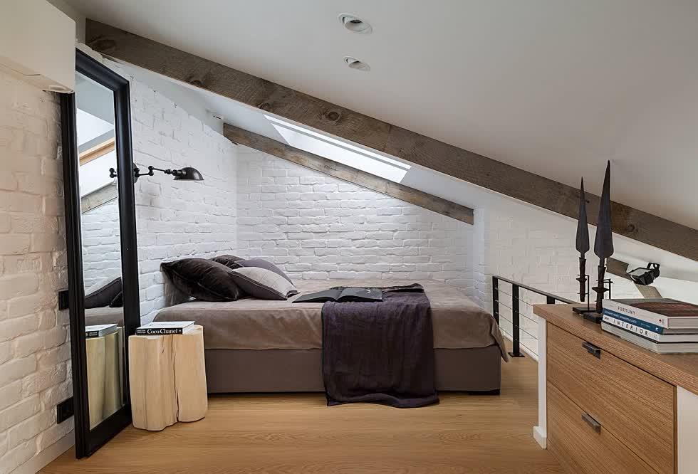 Phòng ngủ gác mái siêu nhỏ với trần dốc và gương lớn giúp nó trông rộng rãi hơn.