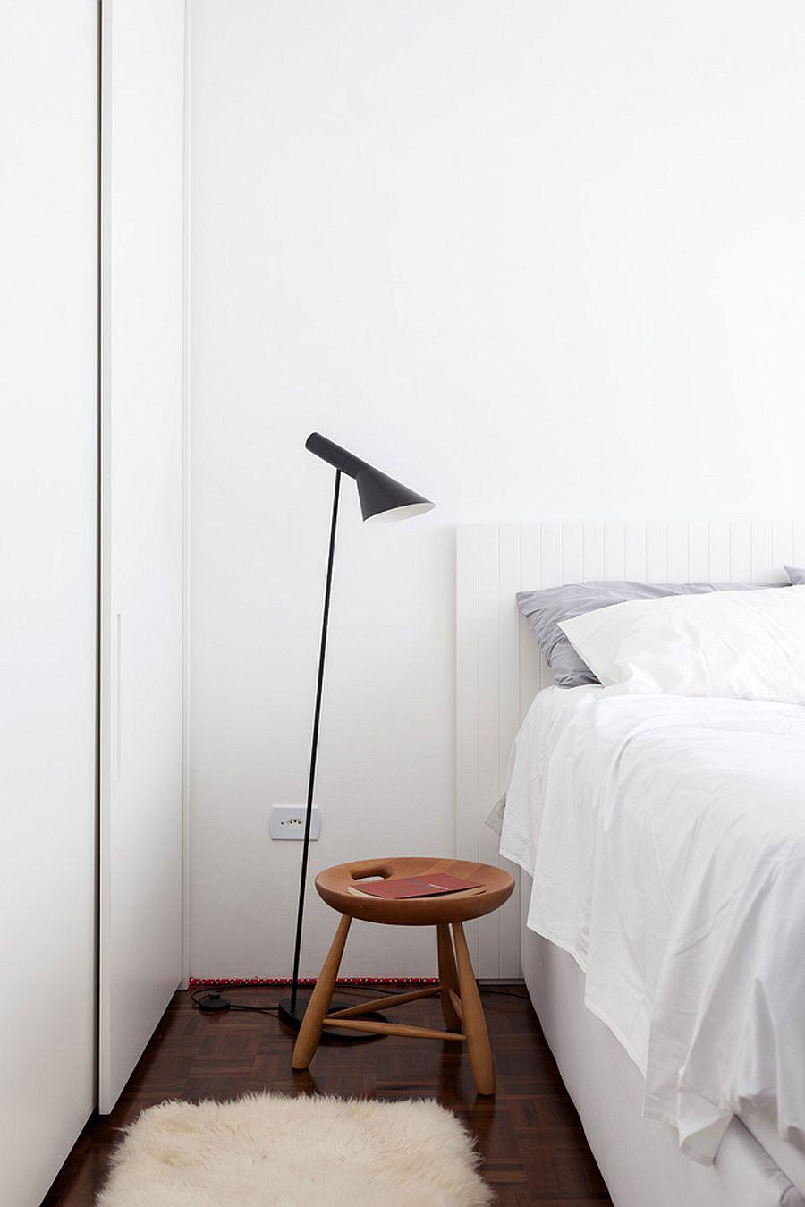 Trong phòng ngủ nhỏ màu trắng, giường chiếm phần lớn diện tích. Đèn sàn màu đen tạo sự tương phản thú vị về mặt thị giác.