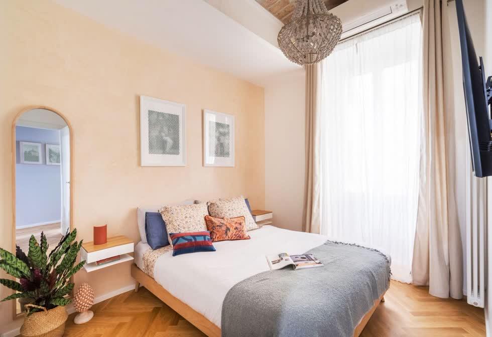 Phòng ngủ master của căn hộ với khung cửa sổ cỡ lớn, tối ưu ánh sáng tự nhiên vào bên trong. Phòng được sơn màu cam đào tạo cảm giác nhẹ nhàng, dễ chịu.