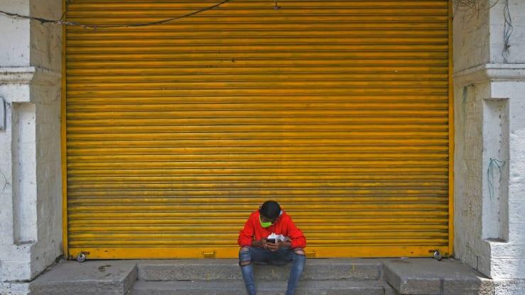 Một người đàn ông ngồi trước cửa hàng bán lẻ đã đóng cửa trên một con phố trong thời gian phong tỏa để ngăn chặn sự gia tăng của các ca nhiễm COVID-19, ở Bangalore. Ảnh chụp vào ngày 20/7/2020. Ảnh: AFP