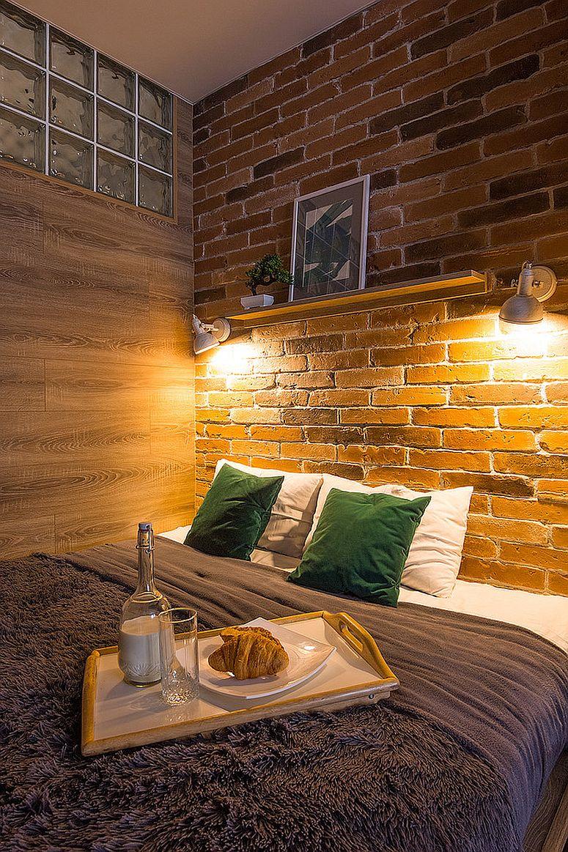Đèn treo chiếu sáng bức tường gạch đầu giường trong phòng ngủ công nghiệp nhỏ.