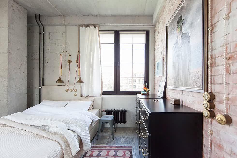 Rèm cửa màu trắng, tường kết cấu và đồ đạc ánh sáng kim loại kết hợp để tạo ra phòng ngủ tuyệt vời này.