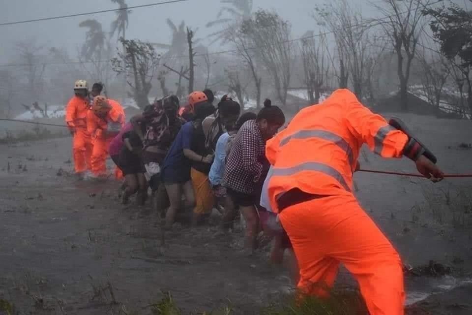 Trong điều kiện mưa ngập và gió mạnh, đội cứu hộ phải cho người dân bám vào sợi dây để di chuyển về phía ôtô đỗ trên đường lớn. Ảnh:Marco Chavez.