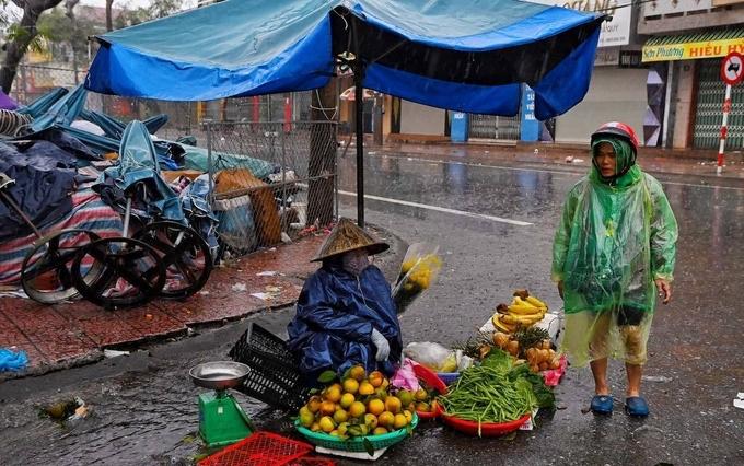 Bất chấp mưa gió, chợ cóc vẫn hoạt động giữa lúc bão đổ bộ. Ảnh: Việt Linh, Giang Huy