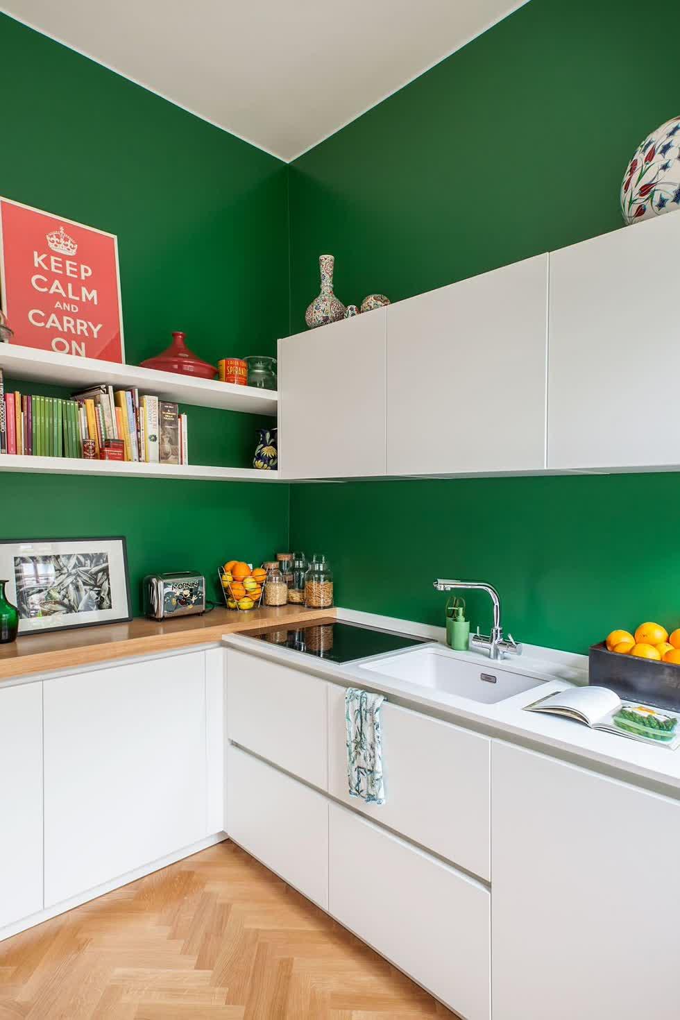 Bức tường màu xanh đậm cho nhà bếp nhỏ theo phong cách Scandinavia với tủ màu trắng.